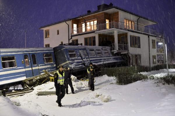 <p>La Policía inspecciona el lugar donde un tren ha colisionado con una vivienda tras descarrilar en Saltsjoebaden a las afueras de Estocolmo, Suecia. (EFE). <br></p>
