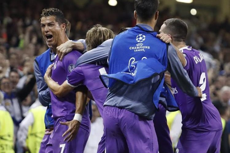 Cristiano Ronaldo es felicitado por sus compañeros luego de su segunda anotación. (Foto Prensa Libre: EFE)