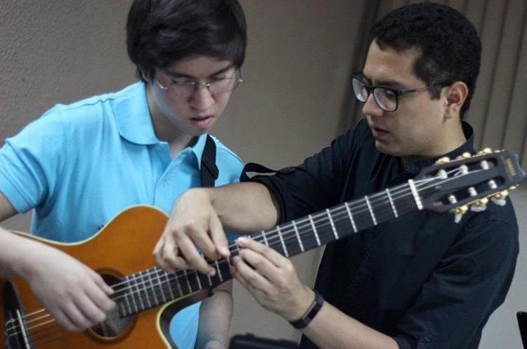 Antonio Monterroso corrige algunos acordes al guitarrista Pablo Monterroso. (Foto Prensa Libre: José Dávila)