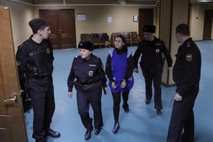 La niñera Bobokúlova (centro), es escoltada por la policía a su llegada al tribunal de distrito de Presnensky en Moscú. (Foto Prensa Libre: EFE).