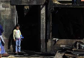 Niña recostada en una de las paredes que no tuvo mayores daños por el fuego que consumió 30 viviendas. (Foto Prensa Libre: Carlos Hernández)