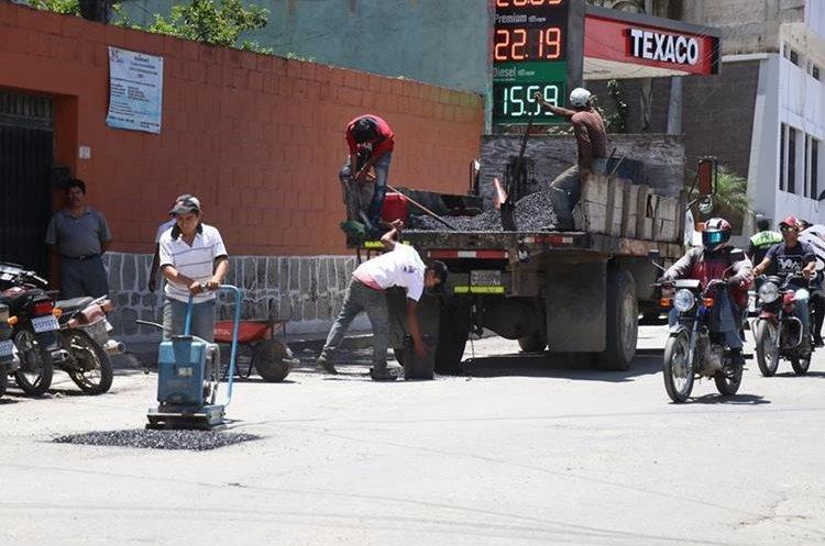 Personal de la comuna de Huehuetenango rellena algunos baches, pues el bacheo efectuado hace poco tiempo no funcionó. (Foto Prensa Libre: Mike Castillo)