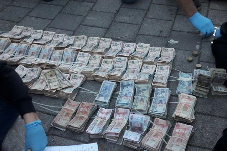 Quetzales y dólares en efectivo que se transportaban en el vehículo del supuesto empresario. (Foto Prensa Libre: PNC)