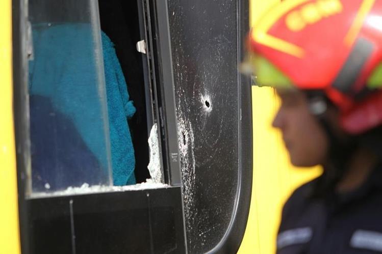 Un orificio de bala se observa en la ventanilla del lado del piloto en el bus pullman atacado este domingo en la calzada Aguilar Batres. (Foto Prensa Libre: Érick Ávila)