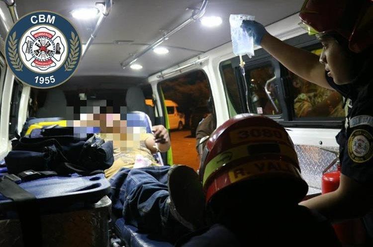 El ayudante del bus atacado en la calzada San Juan es trasladado a un hospital. (Foto Prensa Libre: Bomberos Municipales).