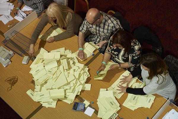 Miembros de una mesa cuentan las boletas para determinar la cantidad de votos. (Foto Prensa Libre: AFP).