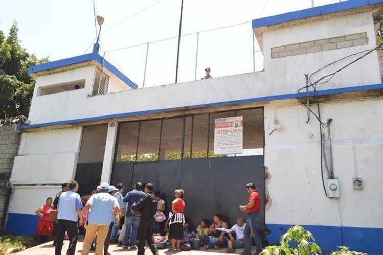 Algunas personas permanecen en el ingreso a la cárcel de El Boquerón, con la intención de dejar alimentos a los internos. (Foto Prensa Libre: Oswaldo Cardona).
