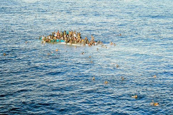 Migrantes tratan de ponerse a salvo luego que el barco en el que viajaban casi se hunde. (Foto Prensa Libre: EFE).