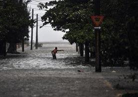 Una persona camina en una de las calles inundadas de La Habana, la capital cubana. (Foto Prensa Libre: AFP)