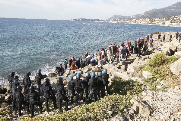 Un grupo de inmigrantes es vigilado por la policías italianos. (AP).