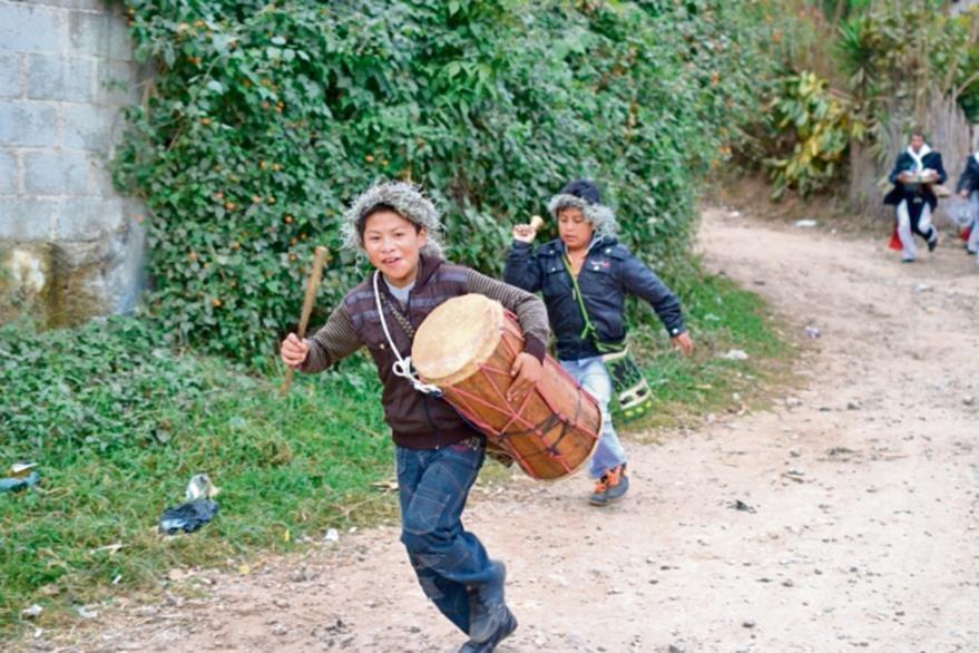Niños con  un tambor y coronas de paxte acompañan a los cofrades en su recorrido. (Foto Ángel Elías)