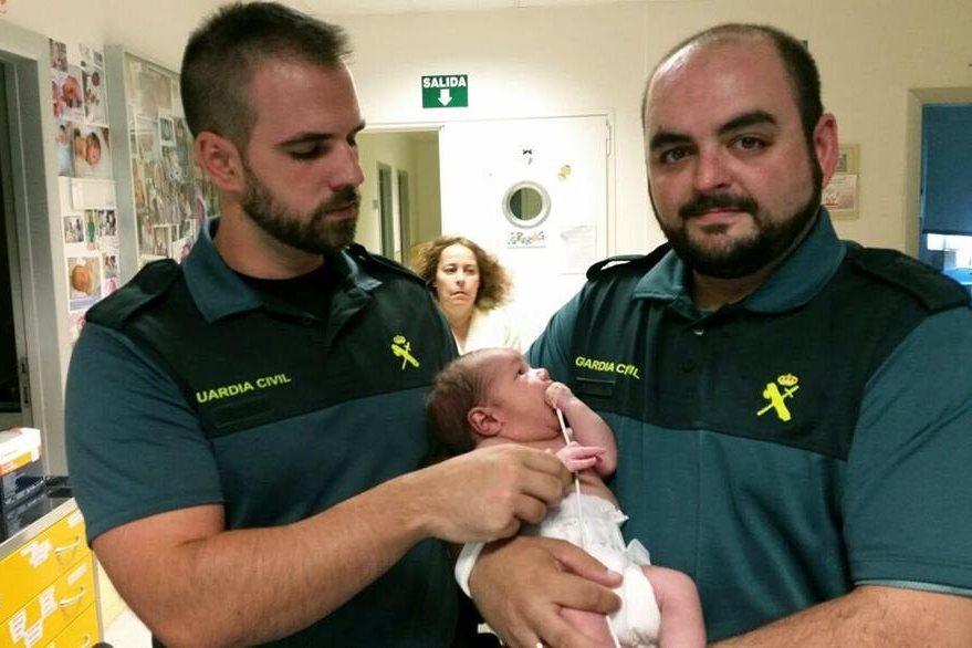 Los dos agentes de la Guardia Civil Española sostienen al bebé horas después de que fue rescatado de un contenedor de basura. (Foto Prensa Libre: EFE).