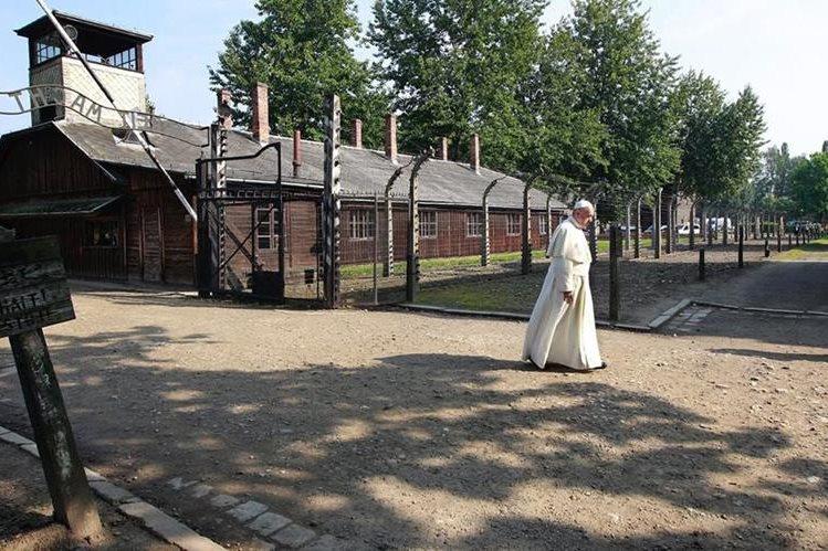 El papa Francisco camina a través de las celdas nazi en Auschwitz. (Foto Prensa Libre: AP).