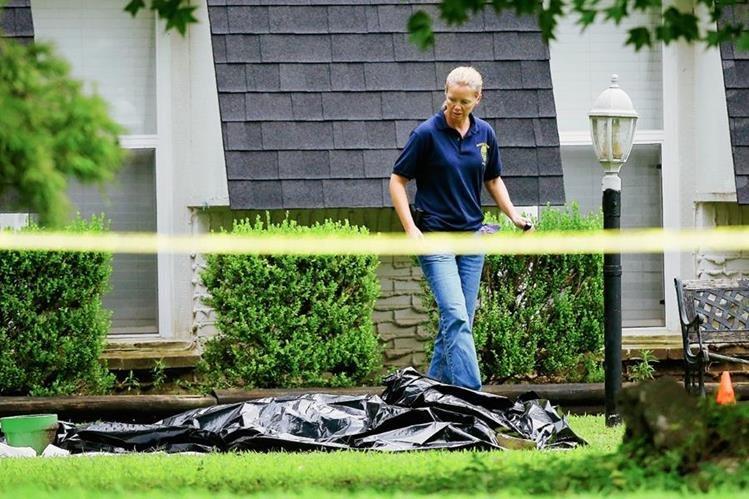 Un investigador observa uno de los cadáveres hallados por la Policía. (Foto Prensa Libre: AP).
