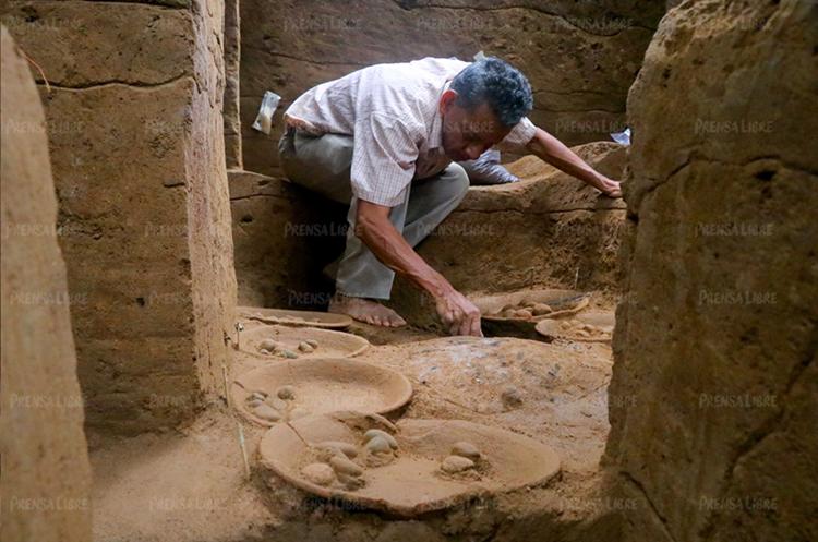 Un excavador limpia el área donde fueron localizados los platos ceremoniales en la cuenca del ombligo de Tak