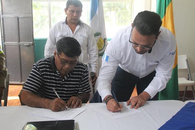 El diputado suplente al Parlamento Centroamericano, Felipe Sac y uno de los representantes de Energuate firman el convenio. (Foto Prensa Libre: Ángel Julajuj)