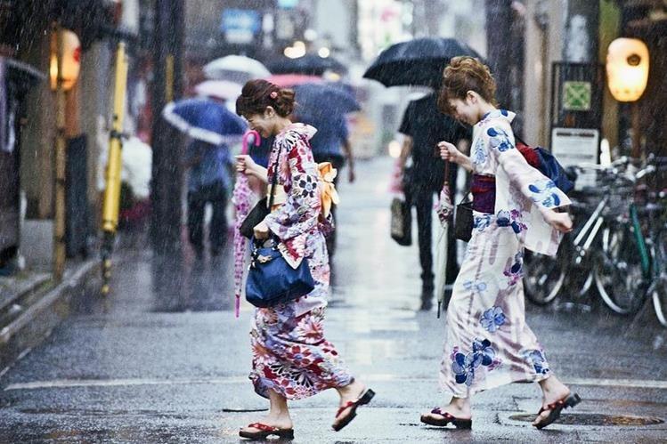 Dos mujerescorren bajo la lluvia del tifón Nangka en una calle de Kyoto, Japón. (Foto Prensa Libre: EFE).