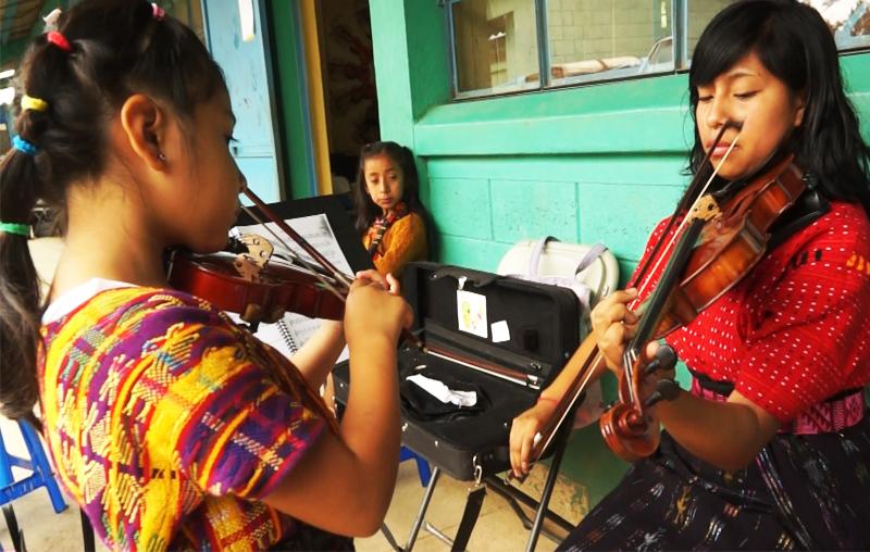 Una joven enseña a una niña las técnicas del violín. (Foto Prensa Libre: Josué León)