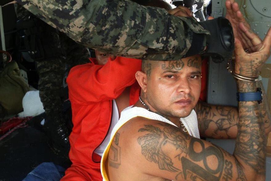 Un líder de la Mara 18 es trasladado por la Policía y el Ejército. (Foto Prensa Libre: AFP).