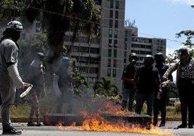 Manifestantes opositores se enfrentan a agentes de la Guardia Nacional Bolivariana mientras bloquean una calle en rechazo a las elecciones de la Asamblea Nacional Constituyente. (Foto Prensa Libre: EFE)