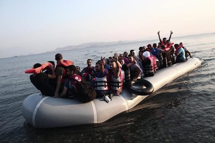 """Migrants flash the """"V for Victory"""" sign as they arrive in a boat on a beach on the Greek island of Kos, after crossing a part of the Aegean Sea between Turkey and Greece, on August 11, 2015. The number of migrants and refugees arriving on Greece"""