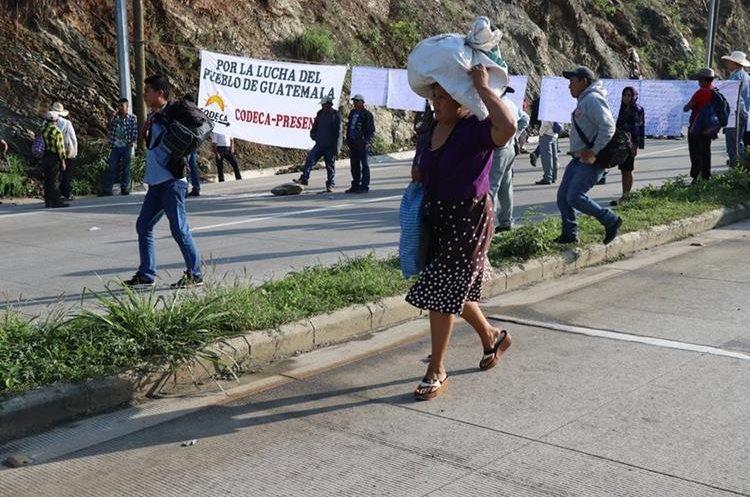 Una mujer afectada por el bloqueo pasa una de las barricadas con su carga en la cabeza con el fin de buscar transporte en uno de los lados de la ruta.