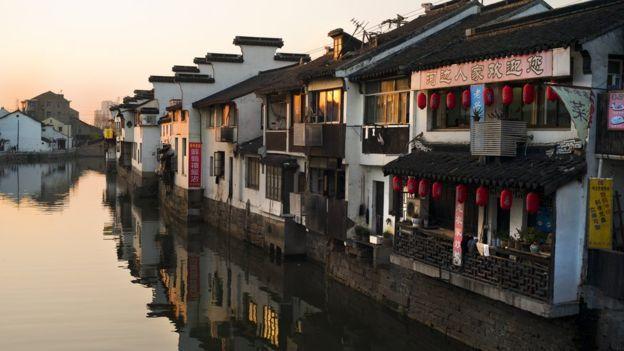 Las copias de puentes occidentales contrastan con las casas tradicionales que se abren paso en el Gran Canal de Suzhou. ROB SMITH/GETTY IMAGES