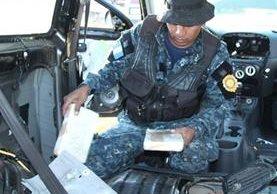 Un agente antinarcótico de la Policía Nacional Civil inspecciona uno de los vehículos localizados en el predio del Organismo Judicial de Cantel. (Foto Prensa Libre: PNC)