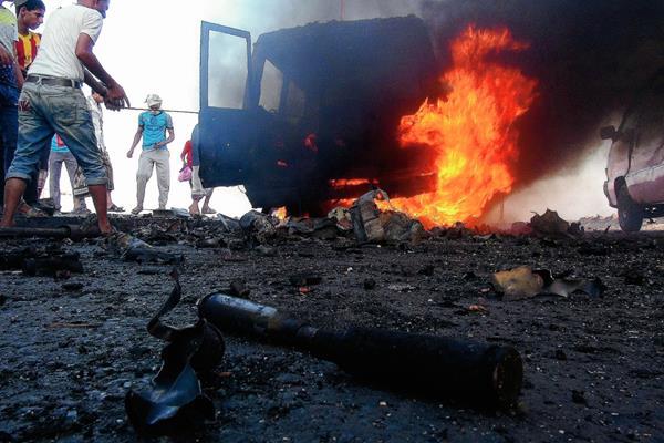 Yemeníes se reúnen cerca a un vehículo incendiado supuestamente perteneciente a rebeldes en Saná. (Foto Prensa Libre:EFE)