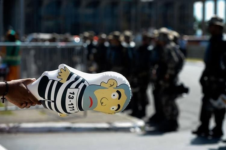 An activist shows a balloon depicting Brazilian former Presidnet Luiz Inacio Lula Da Silva in front of a line of policemen during a demo in support of the impeachment of Brazilian President Dilma Rousseff outside the National Congress in Brasilia, on April 17, 2016.  Rousseff risks being driven from office if the lower house votes in favor of an impeachment trial Sunday. / AFP PHOTO / ANDRESSA ANHOLETE