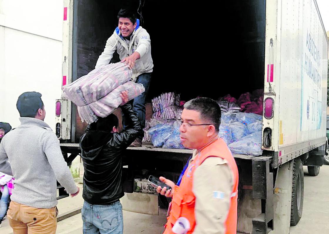 Delegados de la Coordinadora Nacional para la Reducción de Desastres y la Municipalidad de Huehuetenango descargan raciones.(Foto Prensa Libre: Mike Castillo)