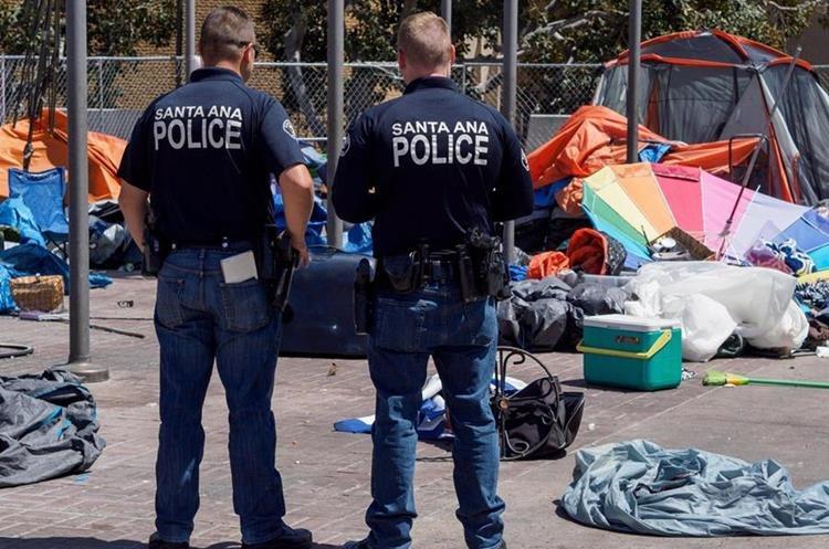 Efectivos de la policía miran los restos de un campamento de personas sin hogar del Condado de Orange. (EFE).