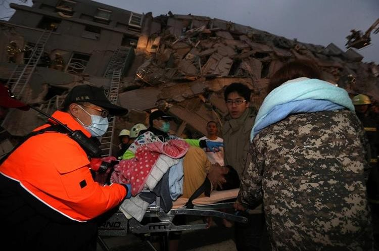 Rescue personnel carry a survivor at the site of a collapsed building in the southern Taiwanese city of Tainan following a strong 6.4-magnitude earthquake that struck the island early on February 6, 2016. At least 30 people have been rescued after four buildings collapsed after a shallow quake struck at a depth of 10 kilometres (six miles) around 2000 GMT Friday, according to the US Geological Survey, 39 kilometres northeast of Kaohsiung, the second-largest city on the island and an important port. / AFP / Johnson Liu