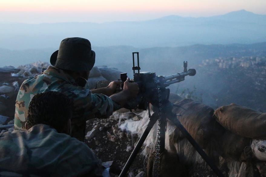 Un miembro del Ejército sirio acciona su metralleta contra posiciones rebeldes en Latakia. (Foto Prensa Libre: AP).