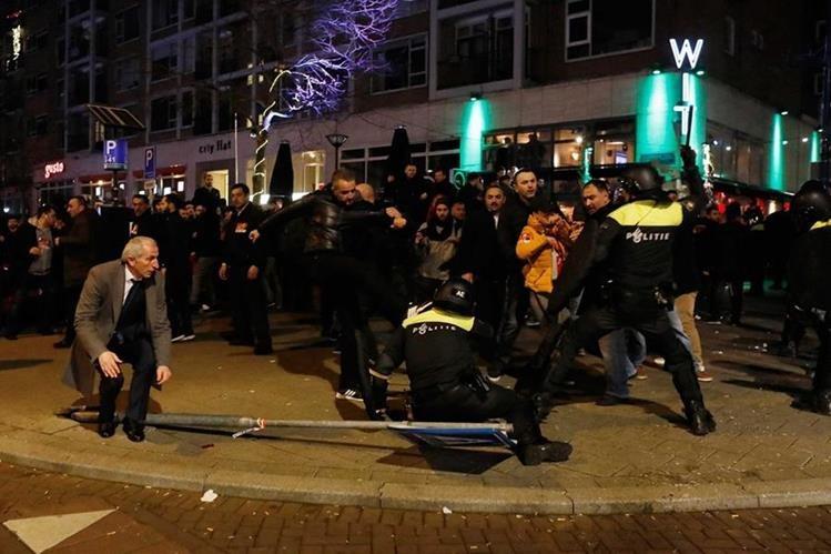 Manifestantes se enfrentan a la policía holandesa frente a la embajada de Turquía en Róterdam. (Foto Prensa Libre: EFE)