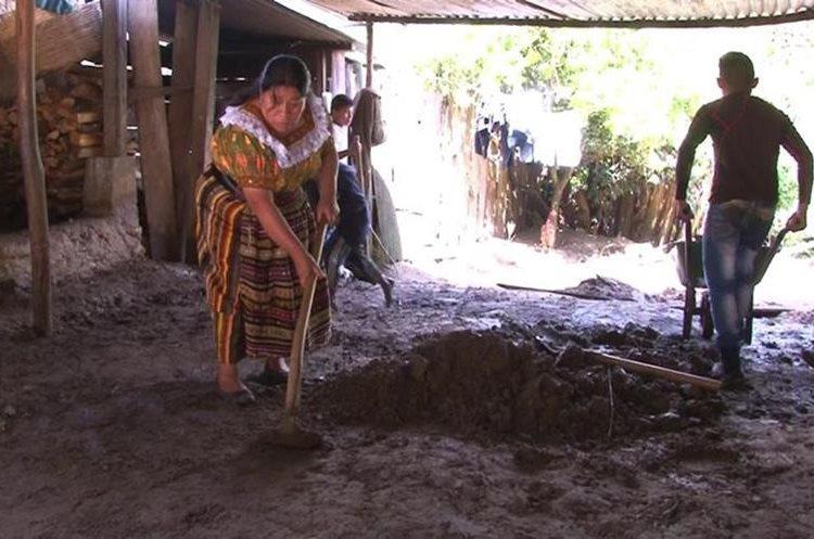 Una madre de familia saca el lodo de su vivienda, la cual fue inundada por el río Negro. (Foto Prensa Libre: Héctor Cordero)