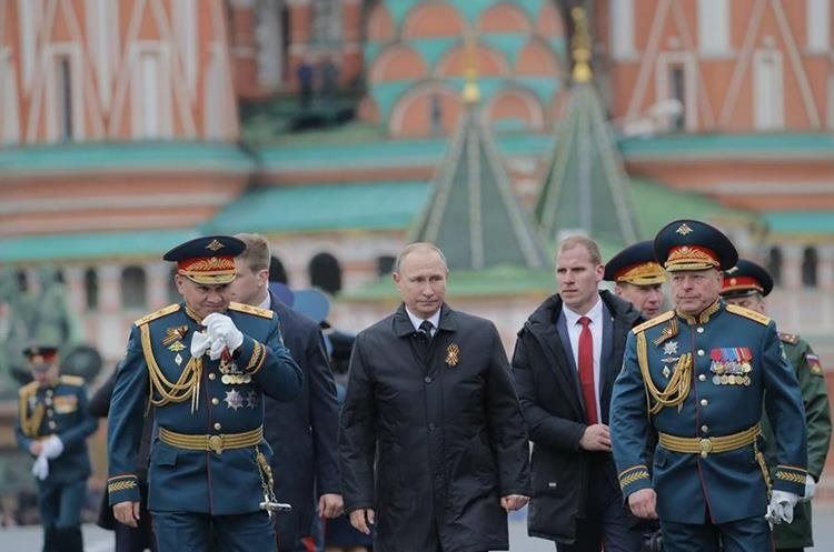 Vladímir Putin (c), y el ministro de Defensa, Serguéi Shoigu (izq), cruzan la Plaza Roja tras el desfile militar.(EFE).