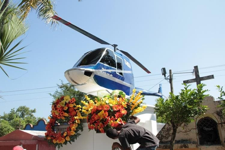La madre de Mario Arreaza cumple el último deseo de su hijo al colocar sobre su tumba la réplica de un helicóptero. (Foto Prensa Libre: Víctor Gómez)