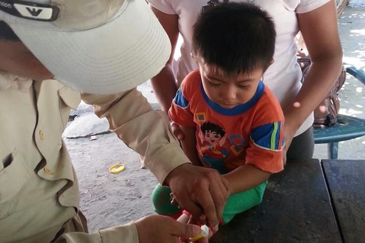 Representante del Área de Salud de Santa Rosa toma una muestra de sangre a un niño, para diagnosticar la enfermedad. (Foto Prensa Libre: Oswaldo Cardona)