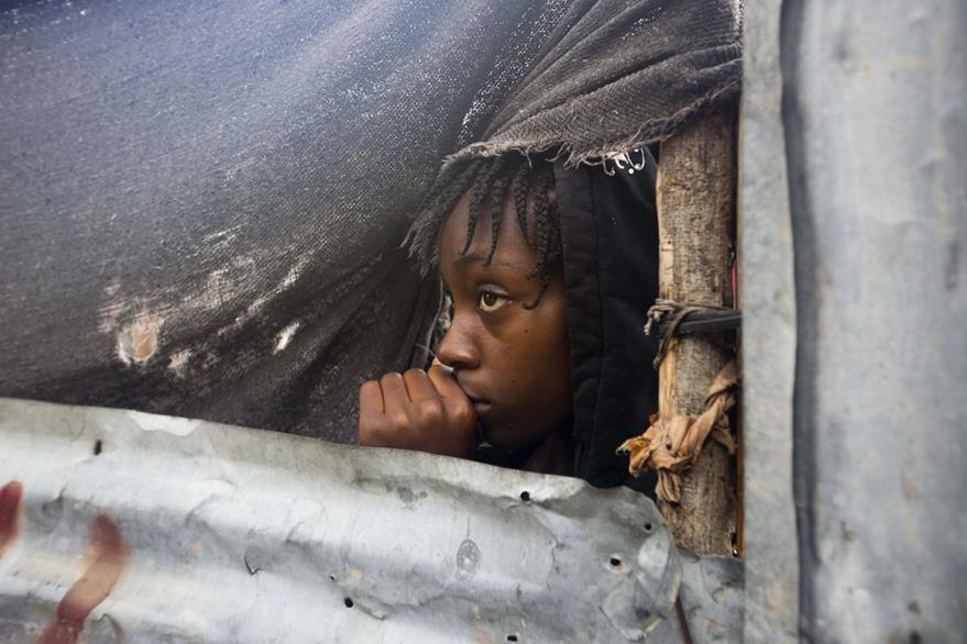 Una niña observa temerosa los devastadores efectos de Matthew, en Haití. AP
