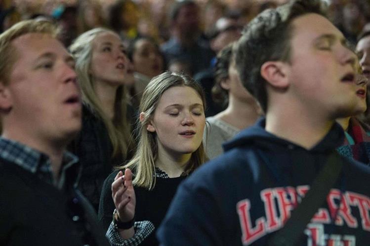 Un grupo de jóvenes canta rock cristiano durante el acto en el que Donald Trump se presentó. (Foto Prensa Libre: AFP).