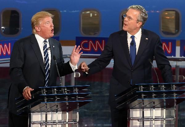 Donald Trump, (izq), y Jeb Bush hablan durante el debate.