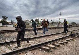 Migrantes corren para recibir alimento en un centro comunitario en la comunidad de Caborca, Sonora, México. (Foto Prensa Libre: AFP).