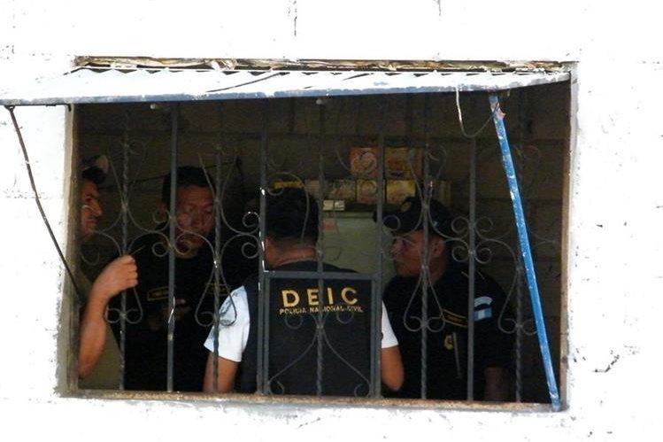 Agentes de la PNC recaban evidencias dentro de un expendio de licor en Sanarate, donde fueron ultimadas dos personas. (Foto Prensa Libre: Héctor Contreras)