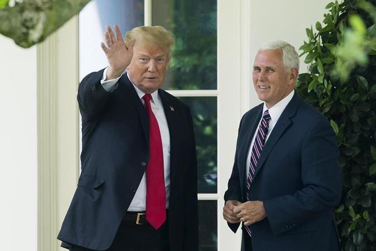 Donald Trump saluda a los medios junto al vicepresidente Mike Pence mientras se dirige hacia el jardín sur de la Casa Blanca