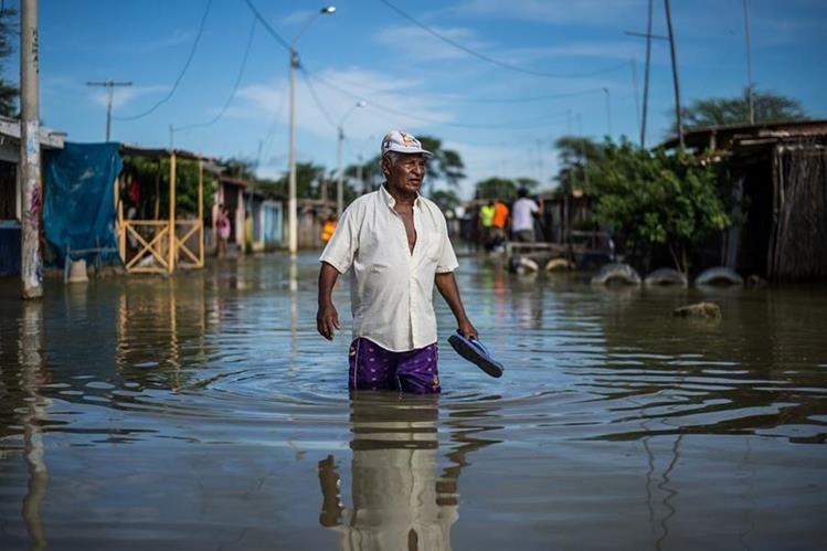 """Un residente de Piura, Perú, es uno de los afectados por la inundación en la calle de """"El Indio"""". (Foto Prensa Libre: AFP)"""