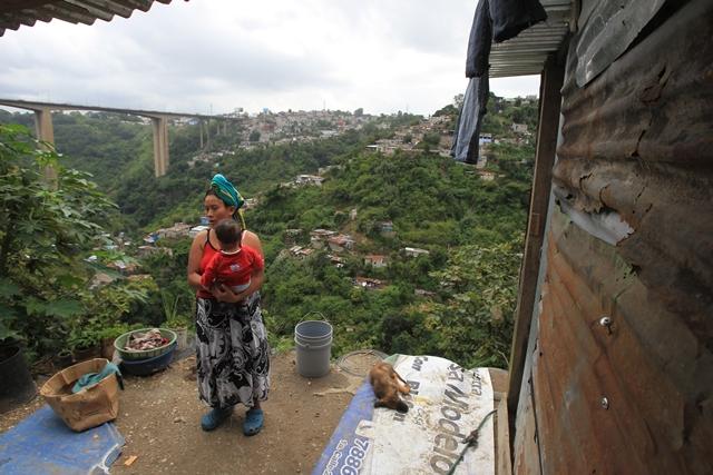 Romelia Gutiérrez carga a su hijo en el patio de su casa, en un barranco de la zona 7 capitalina. El peligro es evidente. (Foto Prensa Libre: Esbin García)