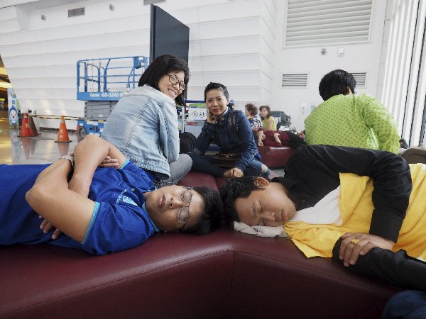 """Dos pasajeros duermen mientras varios vuelos han sido cancelados por el tifón """"Megi"""".(EFE)."""