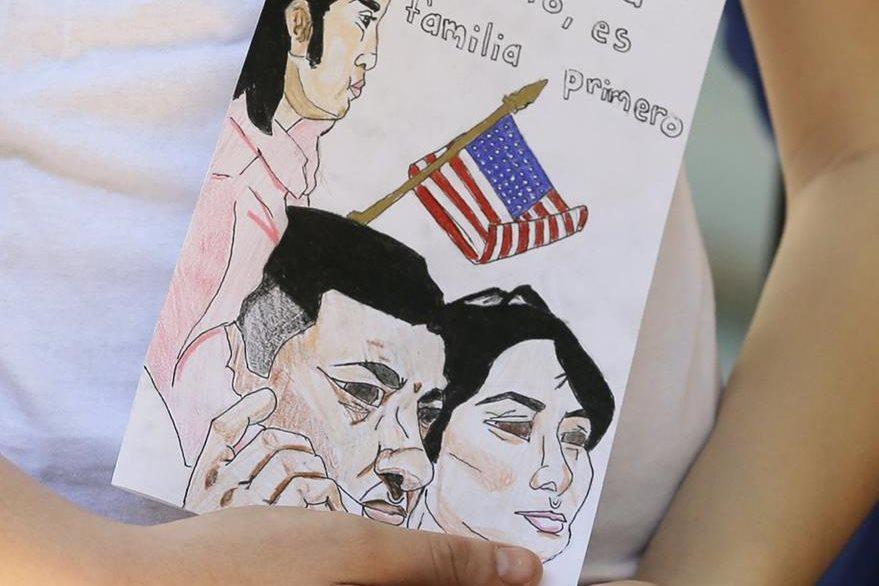 Un niño sostiene un cartel que dice: No es América primero, es la familia primero en el condado de Miami-Dade. (AP).