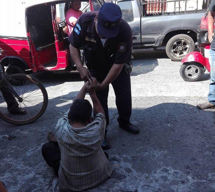Un agente municipal retiene al indigente acusado de tirar basura en una calle de la zona 2 de Mazatenango. (Foto Prensa Libre: Cristian Icó)